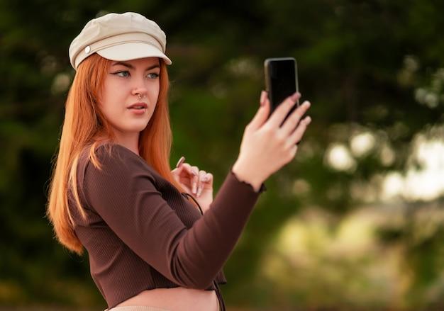Jovem ruiva caucasiana com um chapéu fazendo uma selfie no parque
