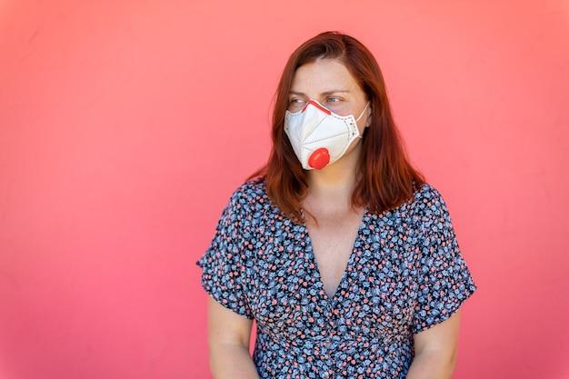Jovem ruiva caucasiana com uma máscara médica protetora de um vírus em rosa