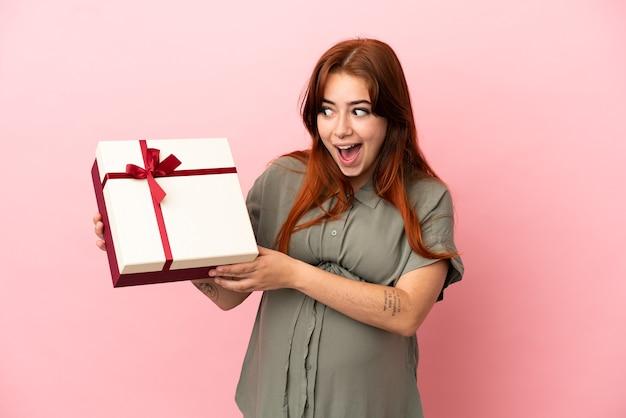 Jovem ruiva caucasiana isolada em um fundo rosa grávida e segurando um presente com expressão de surpresa