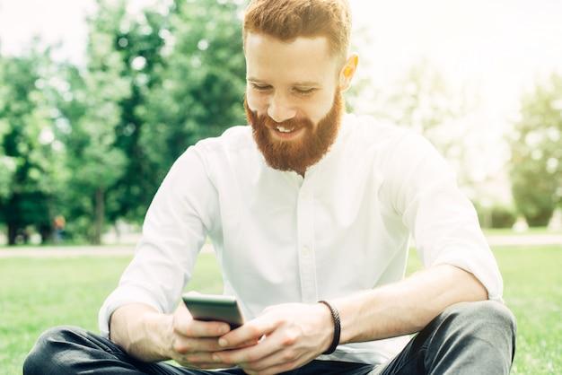 Jovem ruiva com barba em uma camisa branca usa um smartphone enquanto está sentado ao ar livre em um dia ensolarado