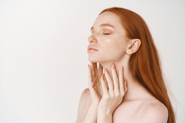 Jovem ruiva com pele pálida e macia, parada de perfil e gostando de tocar o rosto limpo e perfeito, conceito de cuidados com a pele e cosmetologia