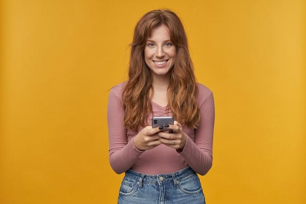 Jovem ruiva com sardas, segurando o telefone com as duas mãos enquanto digita uma mensagem e sorri