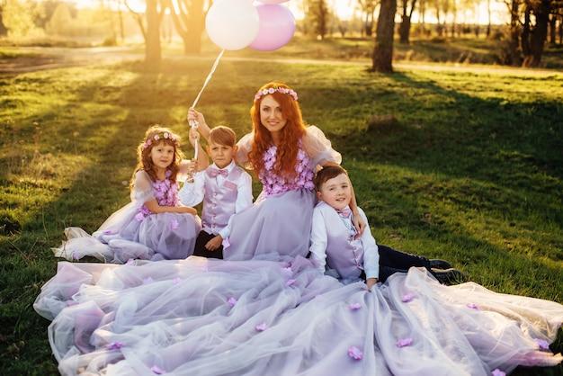 Jovem ruiva com seus filhos em roupas inteligentes, brincando com balões no parque