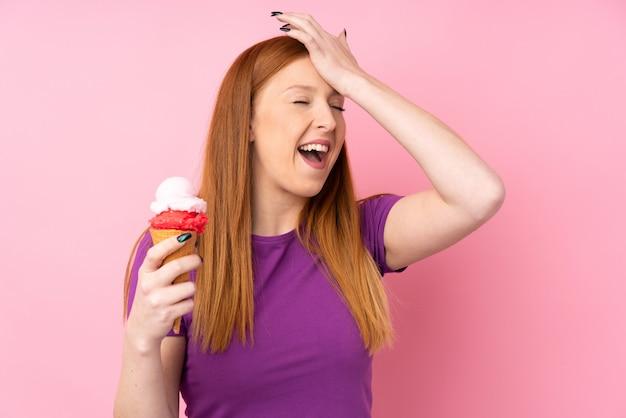 Jovem ruiva com um sorvete de corneta sobre rosa percebeu algo e pretendia a solução