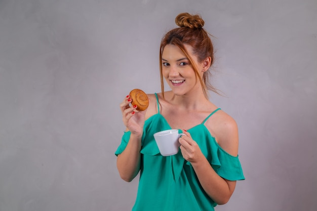 Jovem ruiva comendo rosquinhas e tomando chá no café da tarde