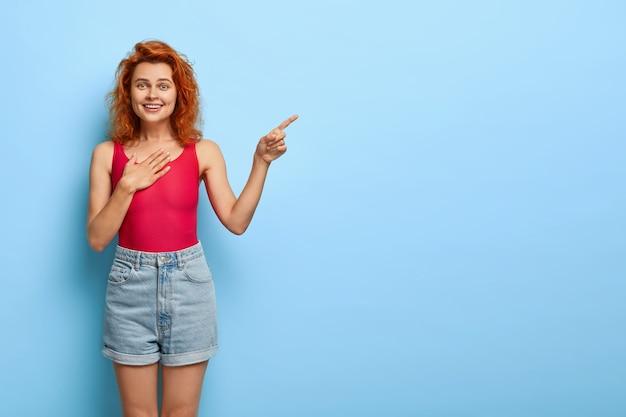 Jovem ruiva de aparência agradável e otimista apontando o dedo para o espaço livre