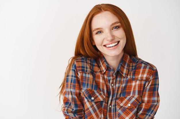 Jovem ruiva de pele pálida e sorriso branco, parecendo feliz na frente, em pé sobre uma parede branca