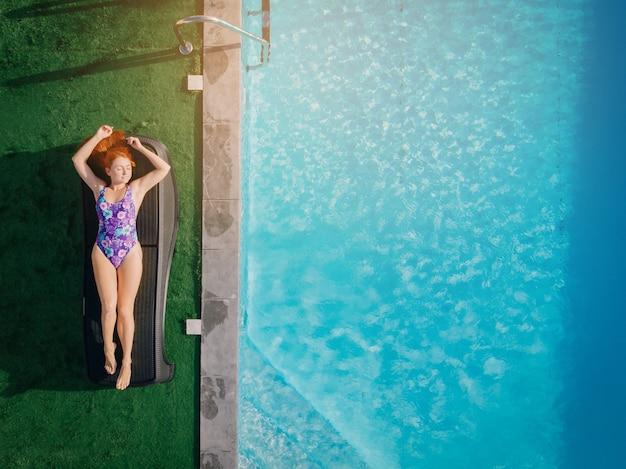 Jovem ruiva descansando em uma espreguiçadeira perto da piscina em um dia ensolarado, vista de cima para baixo