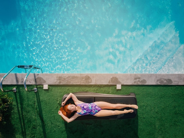 Jovem ruiva descansando em uma espreguiçadeira perto da piscina em um dia ensolarado