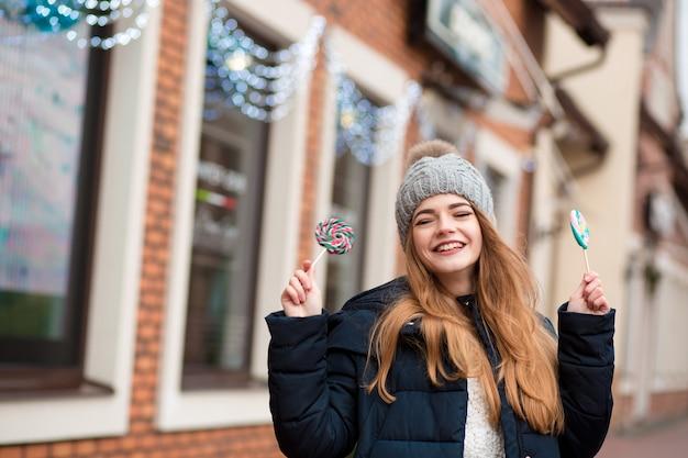 Jovem ruiva descolada usando um chapéu de malha cinza e segurando doces de natal perto da vitrine