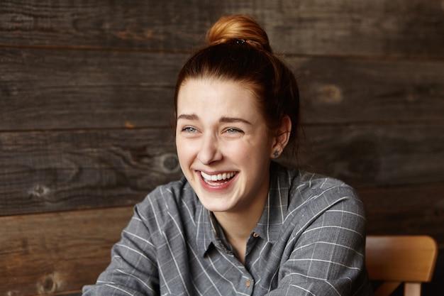 Jovem ruiva elegante vestindo uma camisa xadrez cinza e rindo alto enquanto se diverte dentro de casa