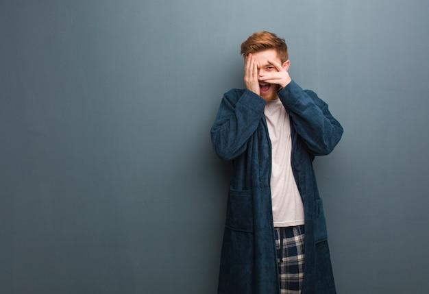 Jovem ruiva em pijama sente-se preocupado e assustado