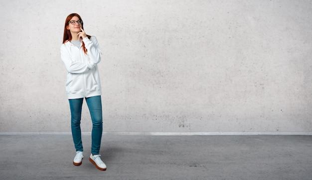 Jovem ruiva em um moletom branco urbano com óculos de pé e pensando