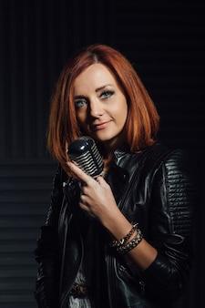 Jovem ruiva em um vestido branco e uma jaqueta de couro preta canta emocionada ao microfone