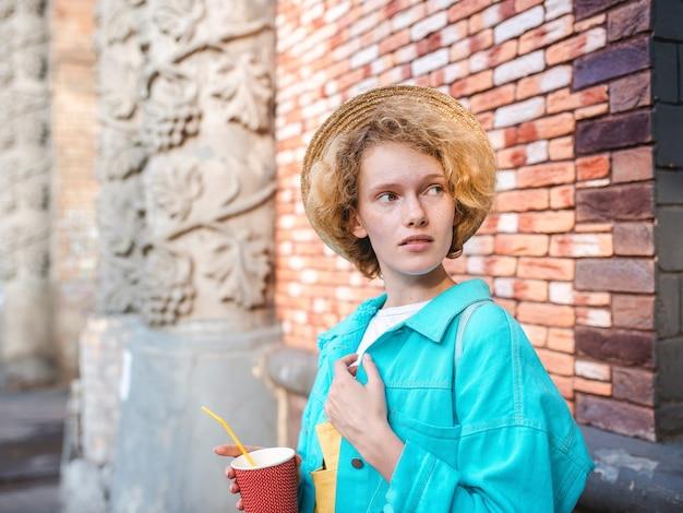 Jovem ruiva encaracolada alegre com casaco azul e chapéu de palha viajante segurando uma xícara de café