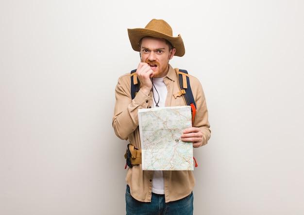 Jovem ruiva explorador homem roer unhas, nervoso e muito ansioso. segurando um mapa.