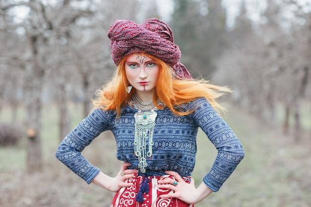 Jovem ruiva extravagante usando joias étnicas, roupas e turbante com maquiagem incomum, dançando ou posando em uma floresta mística ou parque. música trance psicodélica, ioga, conceito esotérico