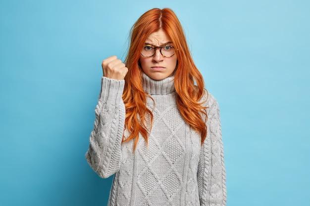 Jovem ruiva fecha o punho com raiva e expressão de descontentamento, vestida com um suéter de malha