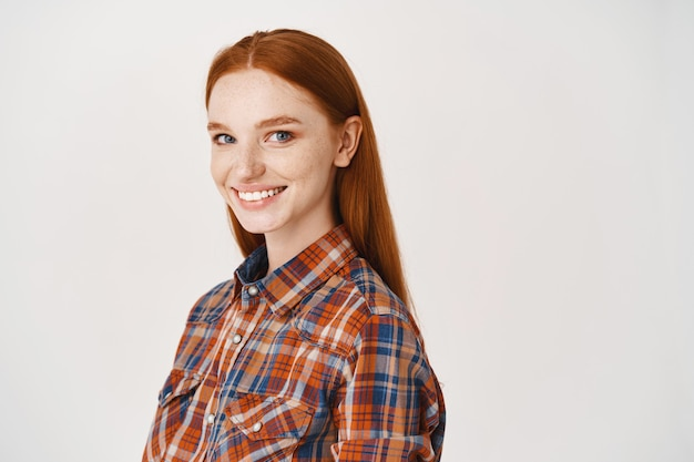 Jovem ruiva feliz com pele clara e sem maquiagem, sorrindo para a frente, em pé sobre uma parede branca
