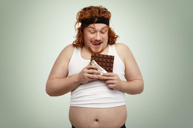 Jovem ruiva feliz no desgaste de esportes segurando a barra de chocolate, prestes a ter um pouco, antecipando seu sabor doce após treino cardio intenso no ginásio. homem obeso com sobrepeso desfrutando de junk food