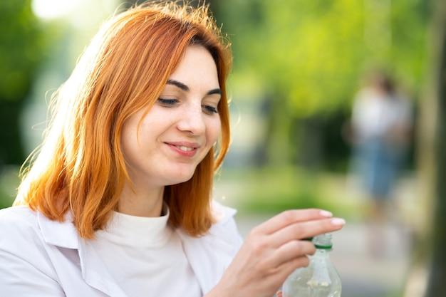 Jovem ruiva feliz segurando a garrafa de água nas mãos no parque de verão.