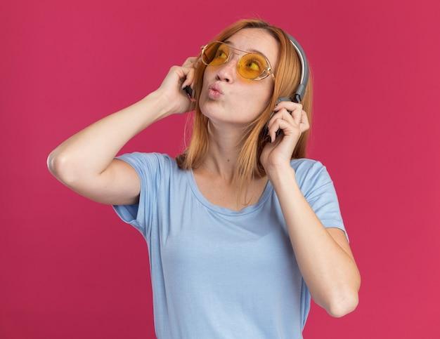 Jovem ruiva impressionada com sardas em óculos de sol e fones de ouvido olhando para o lado