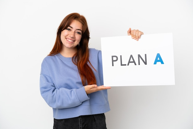 Jovem ruiva isolada em um fundo branco segurando um cartaz com a mensagem plano a com expressão feliz