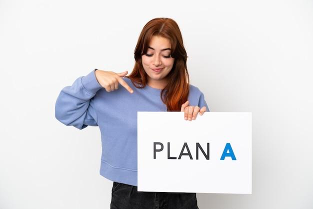 Jovem ruiva isolada em um fundo branco segurando um cartaz com a mensagem plano a e apontando-o