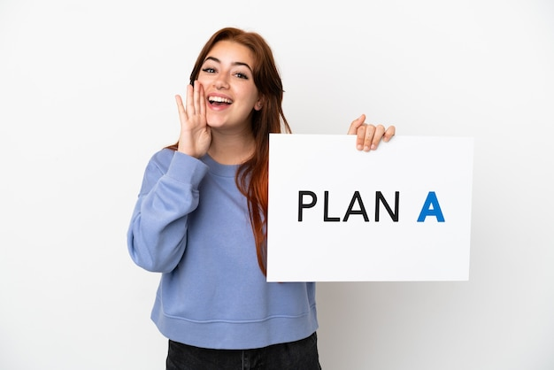 Jovem ruiva isolada em um fundo branco segurando um cartaz com a mensagem plano a e gritando