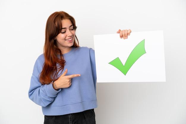 Jovem ruiva isolada em um fundo branco segurando um cartaz com o texto ícone de marca de seleção verde e apontando-o