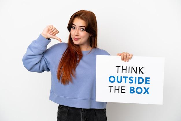 Jovem ruiva isolada em um fundo branco segurando um cartaz com o texto pense fora da caixa com um gesto orgulhoso