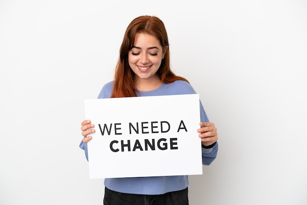 Jovem ruiva isolada em um fundo branco segurando um cartaz com o texto precisamos de uma mudança