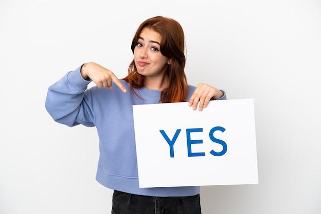 Jovem ruiva isolada em um fundo branco segurando um cartaz com o texto sim e apontando-o