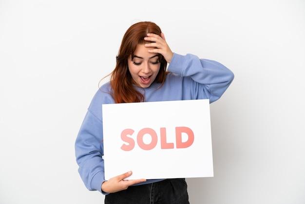 Jovem ruiva isolada em um fundo branco segurando um cartaz com o texto vendido com expressão de surpresa