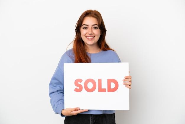 Jovem ruiva isolada em um fundo branco segurando um cartaz com o texto vendido com uma expressão feliz