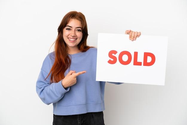 Jovem ruiva isolada em um fundo branco segurando um cartaz com o texto vendido e apontando-o