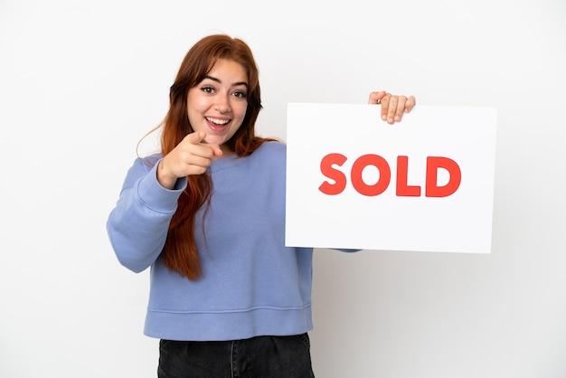 Jovem ruiva isolada em um fundo branco segurando um cartaz com o texto vendido e apontando para a frente