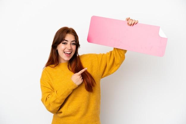 Jovem ruiva isolada em um fundo branco segurando um cartaz vazio e apontando-o