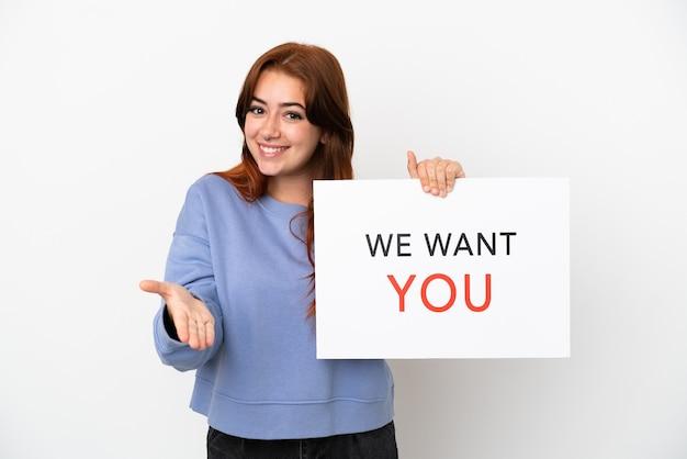 Jovem ruiva isolada no fundo branco segurando a placa we want you fazendo um acordo