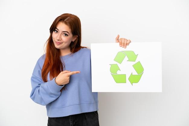 Jovem ruiva isolada no fundo branco segurando um cartaz com o ícone de reciclagem e apontando-o