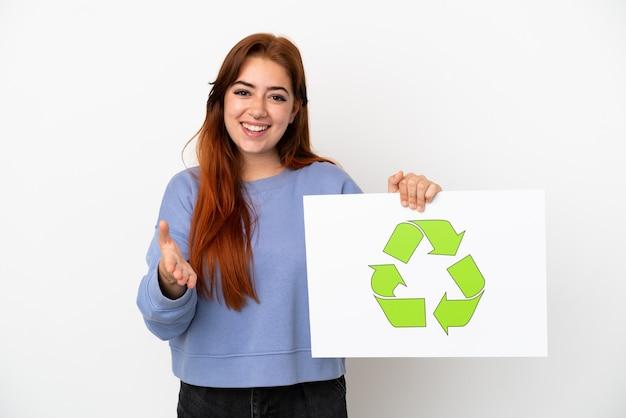 Jovem ruiva isolada no fundo branco segurando um cartaz com o ícone de reciclagem fazendo um acordo