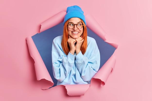 Jovem ruiva linda mantém as mãos embaixo do queixo sorri desvia o olhar com expressão satisfeita e veste roupas azuis rasgando papel