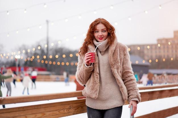 Jovem ruiva linda sardas pista de gelo na. retrato de uma mulher bonita cabelo encaracolado caminhando na feira de ano novo