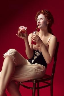 Jovem ruiva medieval como uma duquesa com espartilho preto e roupas de dormir, sentada em uma cadeira no espaço vermelho com uma bebida e donut
