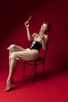 Jovem ruiva medieval como uma duquesa com espartilho preto e roupas de dormir sentada no vermelho