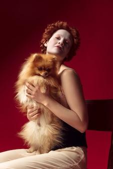 Jovem ruiva medieval como uma duquesa em espartilho preto e roupas de noite, sentada em uma cadeira na parede vermelha com um cachorrinho ou cachorro. conceito de comparação de eras, modernidade e renascimento.