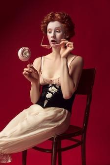 Jovem ruiva medieval como uma duquesa em espartilho preto, óculos escuros e roupa de noite, sentada em uma cadeira na parede vermelha com um doce. conceito de comparação de eras, modernidade e renascimento.