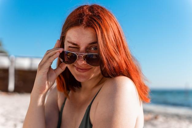 Jovem ruiva olhando através de óculos escuros