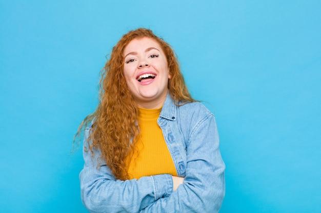 Jovem ruiva parecendo uma empreendedora feliz, orgulhosa e satisfeita, sorrindo com os braços cruzados na parede azul