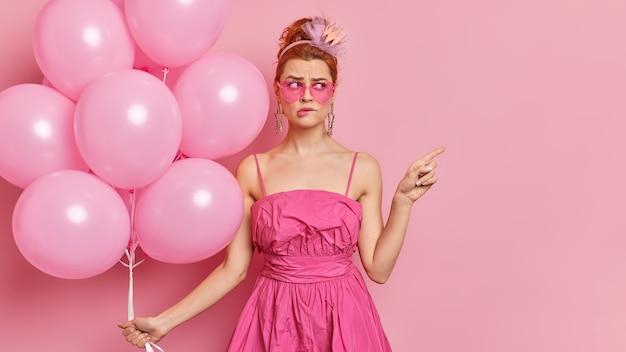 Jovem ruiva perplexa, vestida com roupas glamorosas, usa tudo rosa em poses na festa de galinhas com balões inflados apontando para o espaço vazio morde lábios mostra lugar para seu conteúdo publicitário